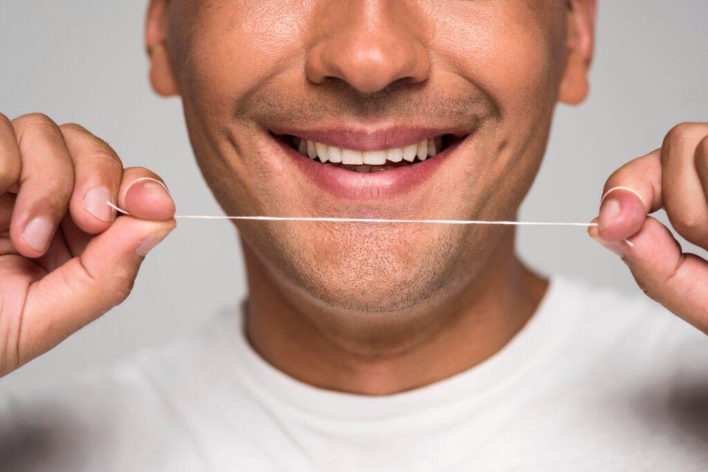 Clínica Dental Sorias - Blog - El uso del hilo dental - Hombre con hilo dental